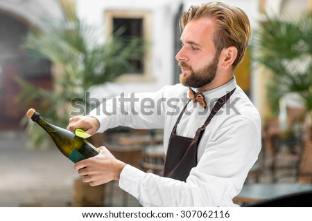 Handsome barman in uniform opening bottle with sparkling wine outdoor on the restaurant terrace. Sabrage - method of opening sparkling wine - stock photo
