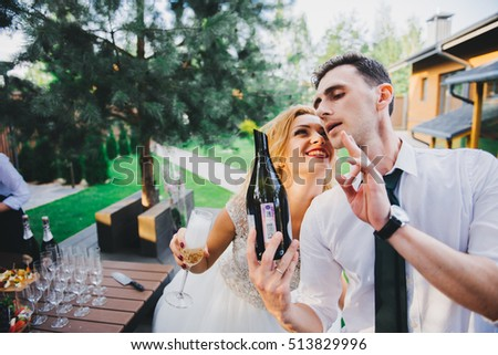 Handsome barman in uniform opening bottle with sparkling wine outdoor on the restaurant terrace. Sabrage - method of opening sparkling wine.wedding tradition, the opening of champagne using a saber