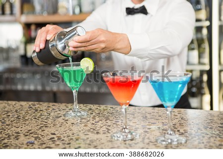 Handsome barman pouring cocktails in a pub - stock photo