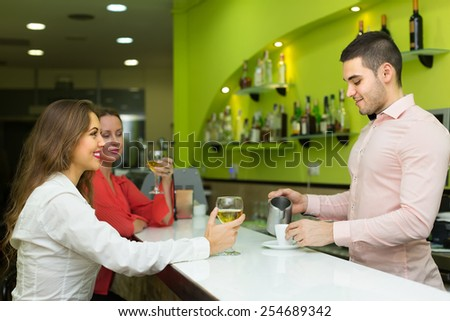 Handsome bartender and two beautiful girls with wine glasses at bar. Focus on girl