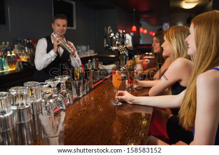 Handsome bartender making cocktails for attractive women in a classy bar - stock photo