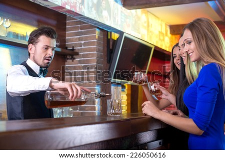 Handsome bartender serving cocktail to attractive woman in a classy bar - stock photo