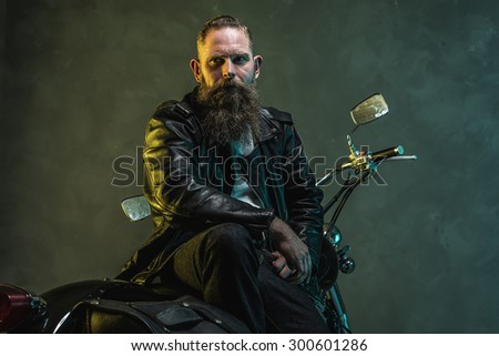 Handsome Bearded Biker Man in Leather Jacket Sitting on his Motorcycle and Looking Into the Distance Against Black Wall Background - stock photo
