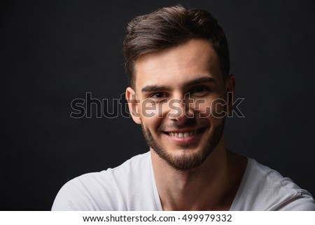 handsome bearded businessman against black background
