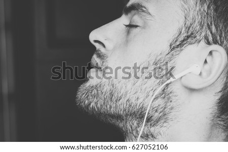 handsome, bearded guy with headphones listening to music