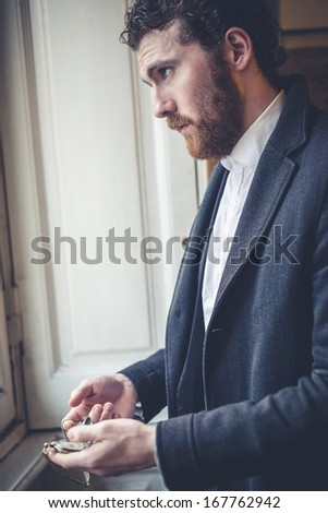 handsome bearded hipster elegant man with pocket watch - stock photo