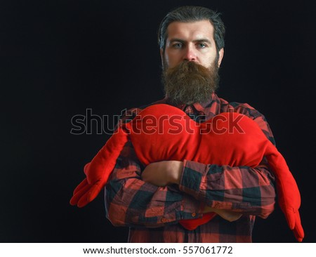 handsome bearded man or guy in checkered shirt with fashionable mustache and beard on serious face holds valentines red heart pillow on black background, copy space