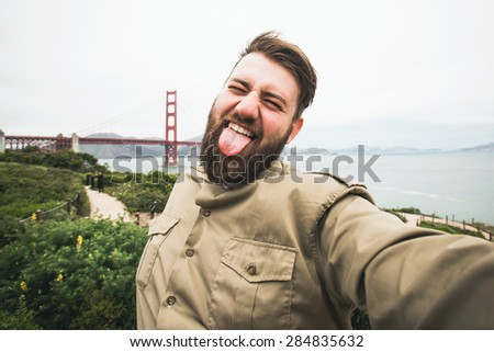 Handsome bearded man tourist laughing and making selfie photo with digital camera near Golden Gate Bridge in San Francisco, California, USA - stock photo
