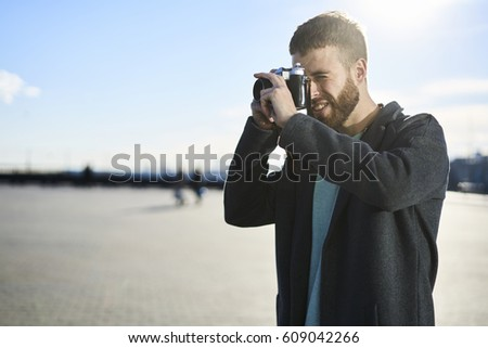 Handsome bearded man tourist making picture of town enjoying weekend journey, talented creative male photographer using vintage camera working outdoors on urban session standing near advertising area