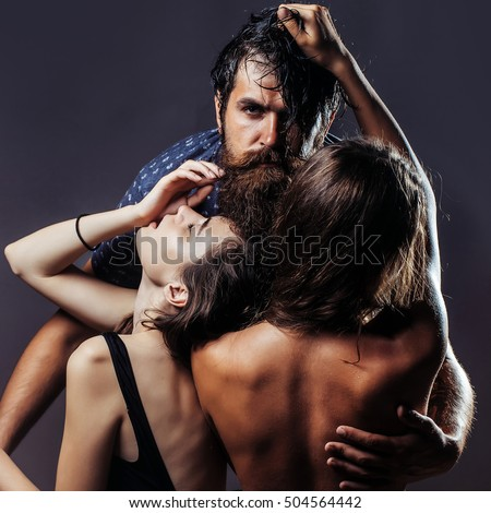 handsome bearded man with beard and pretty girls with naked back posing has bare sexy body in studio on gray background