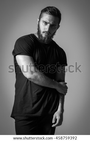 Handsome Bearded Man With Tattoo In Black T-shirt Posing On Background. Model Tests - stock photo