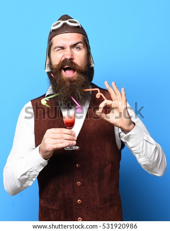 handsome bearded pilot or aviator man with long beard and mustache on funny face holding glass of alcoholic shot in vintage suede leather waistcoat with hat and glasses on blue studio background