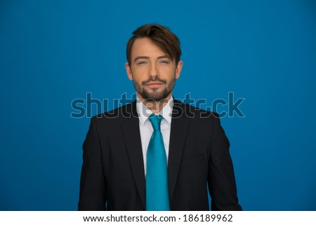 Handsome bearded young businessman in a stylish suit and tie standing looking directly at the camera on a blue background with copyspace - stock photo
