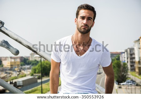 Handsome bearded young man outdoors in urban environment looking at camera - stock photo