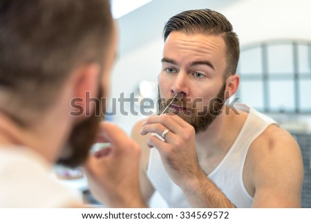 Handsome bearded young man standing plucking his nasal hairs in front of the mirror in the bathroom during his daily grooming - stock photo