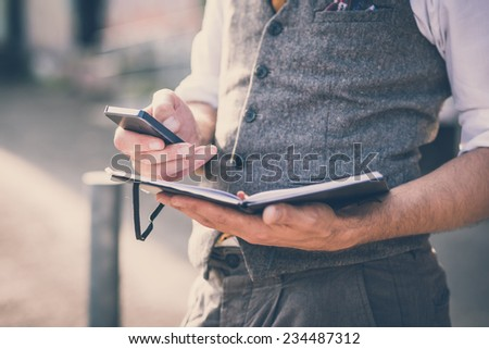 handsome big moustache hipster man with diary and smartphone in the city - stock photo