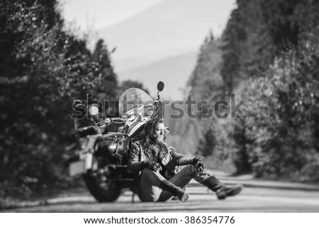 Handsome biker with beard and long hair sitting next to a traveler motorcycle on an open road. Sunny summer day in the mountains. Tilt shift soft effect. Black and white - stock photo