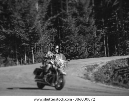 Handsome biker with beard driving his cruiser motorcycle by nice road in the forest. Man is wearing leather jacket, jeans and sunglasses. Tilt shift lens blur effect. Black and white - stock photo