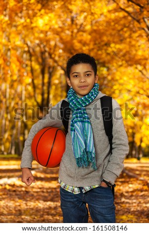 Handsome black boy 10 years old standing in the autumn park under maple trees with orange basketball ball - stock photo