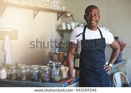 Handsome black entrepreneur stands by cafe counter lined with jars of tea while wearing dark colored apron - stock photo