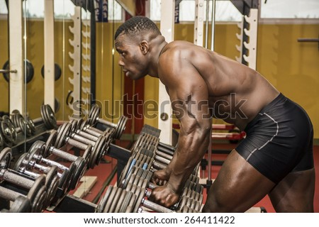 Handsome black male bodybuilder resting after workout in gym, leaning tired on weights - stock photo