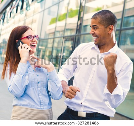 Handsome black man and his partner looking each other while she is talking on mobile phone. They are happy hearing good news. Shallow depth of field. - stock photo