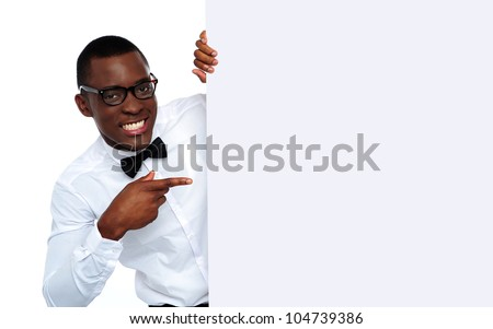 Handsome black man holding blank placard and pointing at it