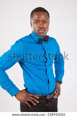 Handsome black man in blue, long sleeve shirt and bow tie his hands on his hips, looking at the camera with a calm, thoughtful and serious expression - stock photo