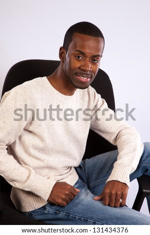 Handsome black man lounging sideways in a chair with one leg over the arm rest and  with a happy, content smile