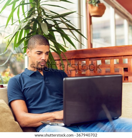 Handsome black man sitting at cafe bar,listening music and typing on laptop. He is looking at computer. - stock photo