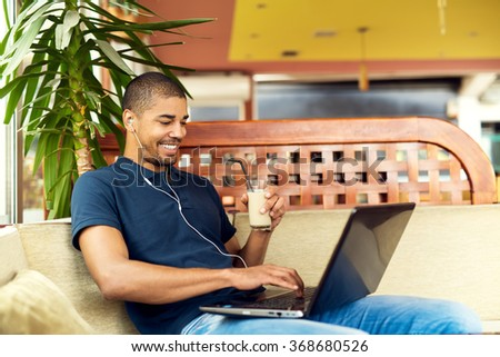 Handsome black man sitting at cafe bar,listening music and typing on laptop. He is looking at computer and smiling. - stock photo