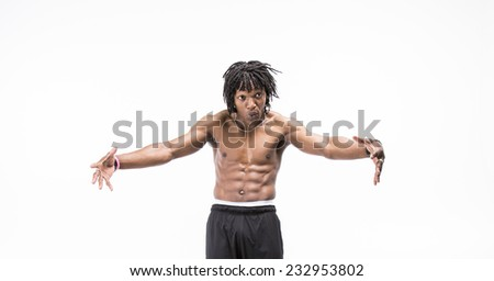 Handsome black man with dreadlocks working out topless wearing all black exercise shorts flexing his abs and leaning back holding his arms out - stock photo