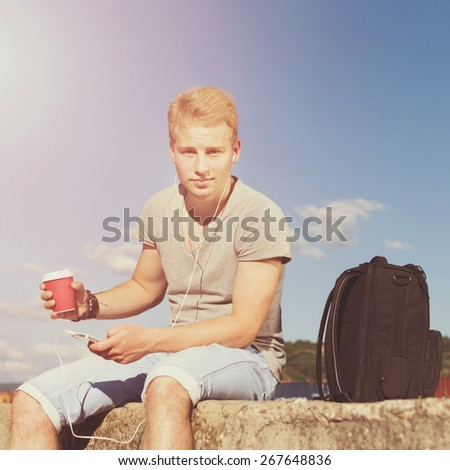 Handsome blond young man with takeaway coffee, smart phone and backpack outdoors on sunny summer sitting and relaxing. Square format image, retouched, filter applied. - stock photo