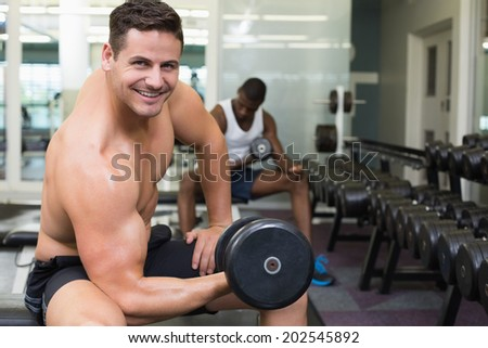 Handsome bodybuilder lifting heavy dumbbell smiling at camera at the gym