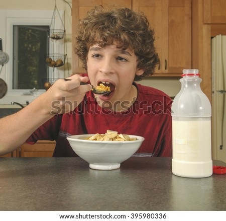 Handsome boy, age twelve, eating cereal for breakfast