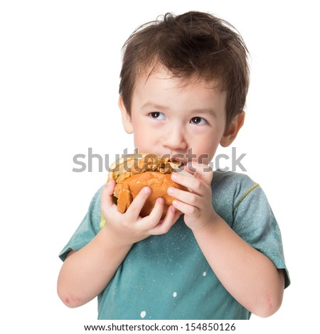 Handsome boy eating a big burger. - stock photo