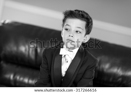 Handsome boy in a tuxedo suit black and white - stock photo