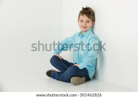 Handsome boy in blue shirt and jeans sitting near wall over white background. Copy space. - stock photo