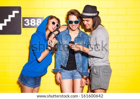 handsome boy in hat shows his cellphone to two beautiful young girls in sunglasses in front of yellow brick wall - stock photo