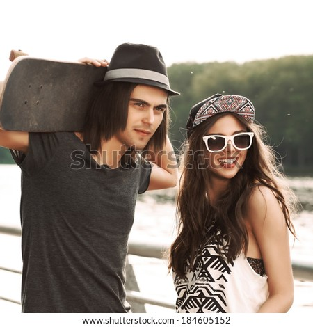 handsome boy in hat with a skateboard on his shoulders and pretty girl in sunglasses stand by river handrail - stock photo