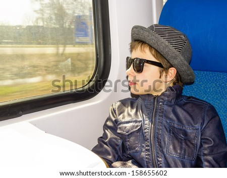 Handsome boy in sunglasses rides on a train - stock photo