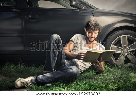 handsome boy reading a book lying on the grass with beautiful car behind him - stock photo