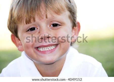 Handsome Boy showing off his perfect smile.  He has blonde hair and brown eyes with a small birth mark on his face. - stock photo