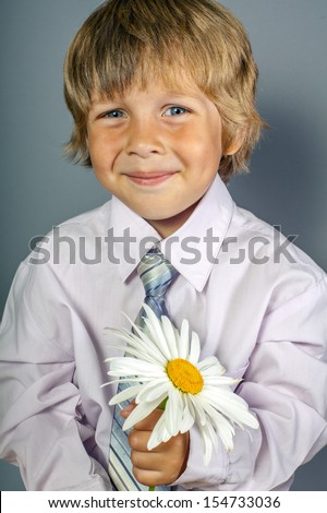 handsome boy wearing classic suit with flowers in hands - stock photo