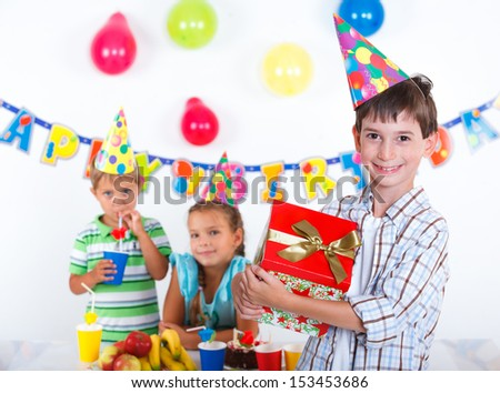 Handsome boy with giftbox looking at camera having fun at birthday party with his friends on background