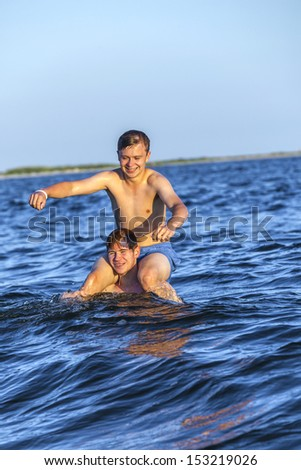 handsome boys have fun playing piggyback in the ocean - stock photo