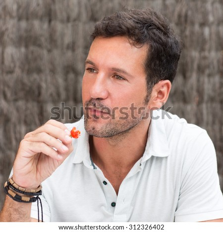 Handsome brunette man eating red strawberry and thinking - stock photo