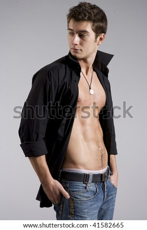 handsome brunette man wearing black shirt and jeans on grey background - stock photo