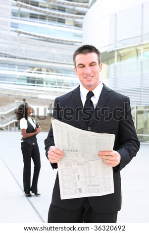 Handsome business man at the office reading a newspaper - stock photo
