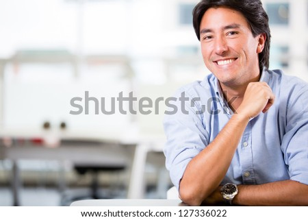 Handsome business man at the office smiling - stock photo
